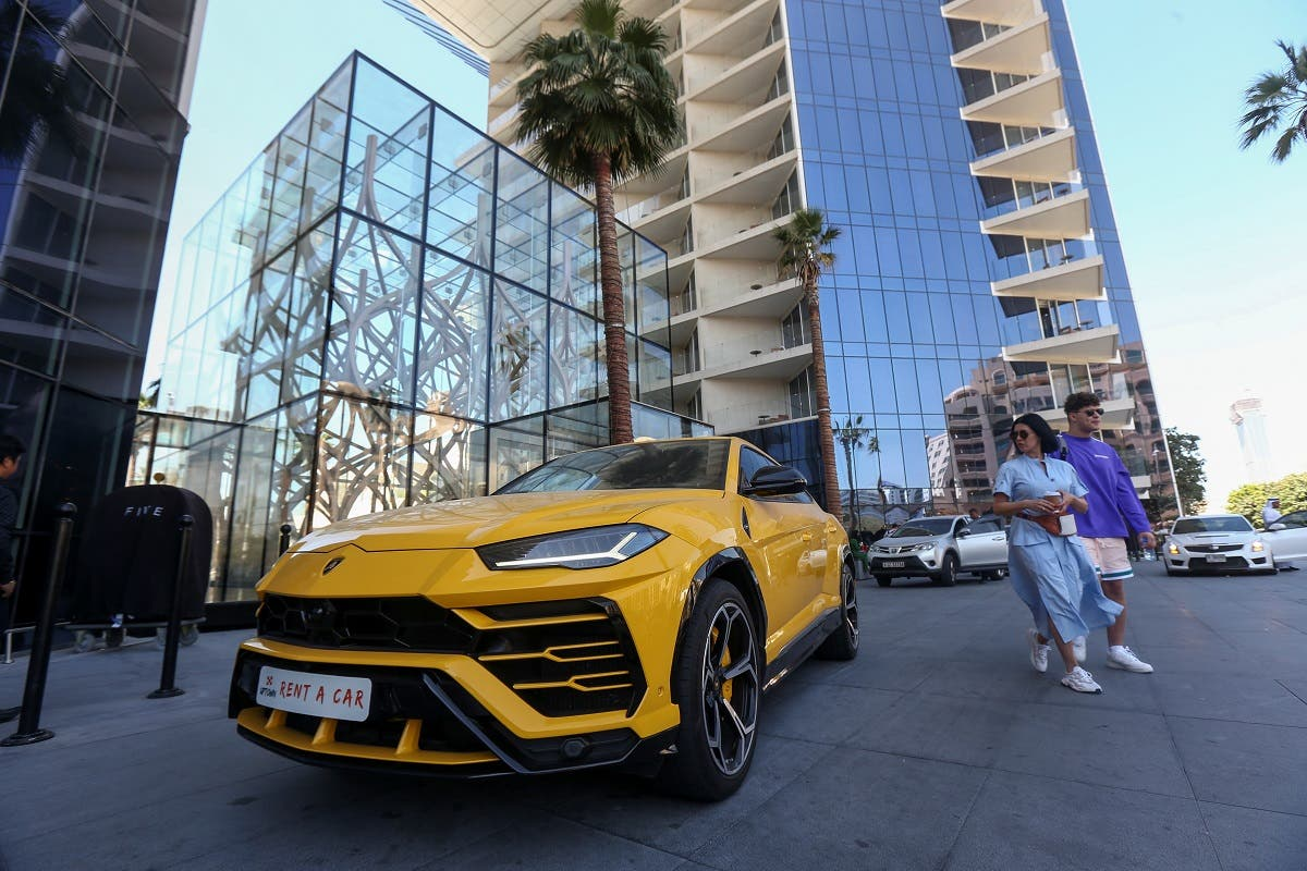 Tourists walk past a luxury rental car parked outside a hotel in Palm Jumeirah in Dubai, United Arab Emirates, March 11, 2020. (Reuters)