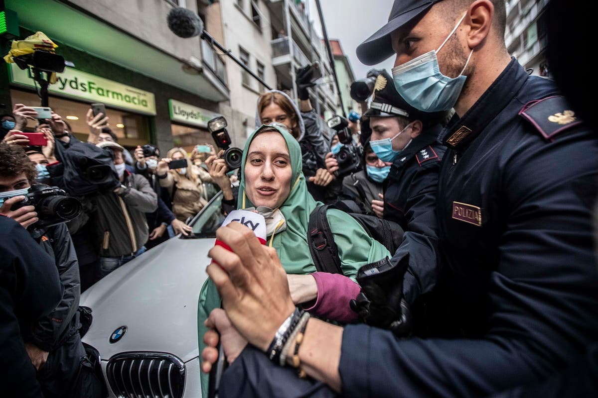 Silvia Romano, escorted by Carabinieri, lowers her face mask for press as she arrives at her home, in Milan, Italy, Monday, May 11, 2020.  (AP)