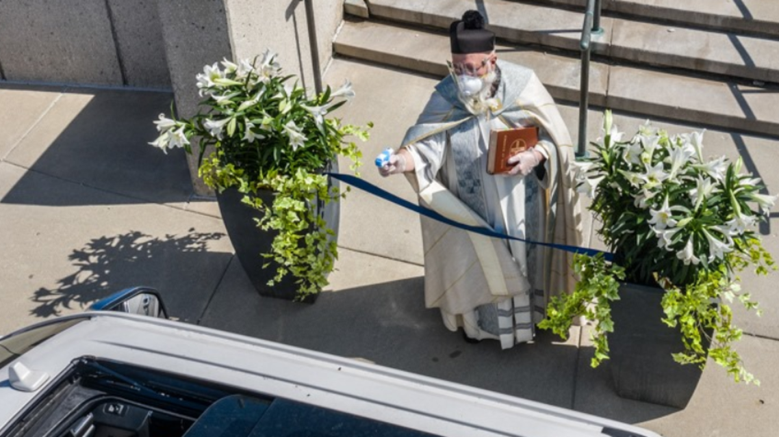 Father Timothy Pelc sprays holy water outside St. Ambrose church in Grosse Pointe Park, Michigan. (Courtesy: Larry Peplin)