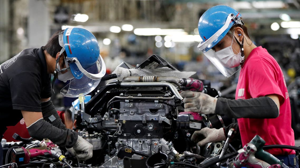 Employees wearing protective face masks and face guards work on the automobile assembly line as the maker ramps up car production with new security and health measures as a step to resume full operations, during the outbreak of the coronavirus disease (COVID-19), at Kawasaki factory of Mitsubishi Fuso Truck and Bus Corp., owned by Germany-based Daimler AG, in Kawasaki, south of Tokyo, Japan May 18, 2020. REUTERS/Issei Kato