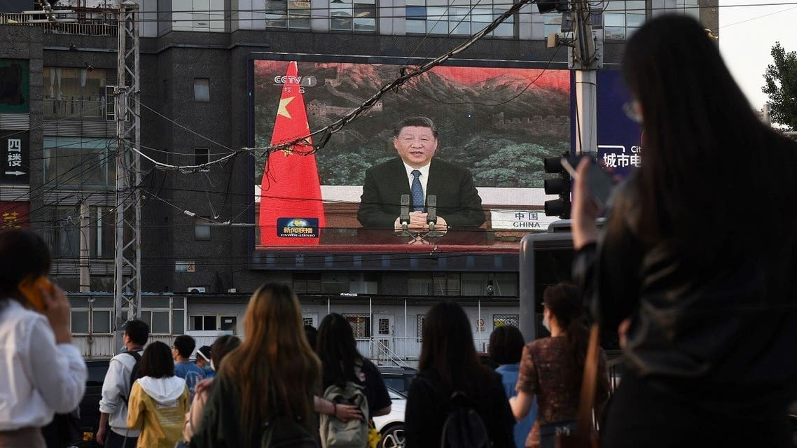 A news program shows Chinese President Xi Jinping speaking via video link to the World Health Assembly, on a giant screen beside a street in Beijing on May 18, 2020. (AFP)