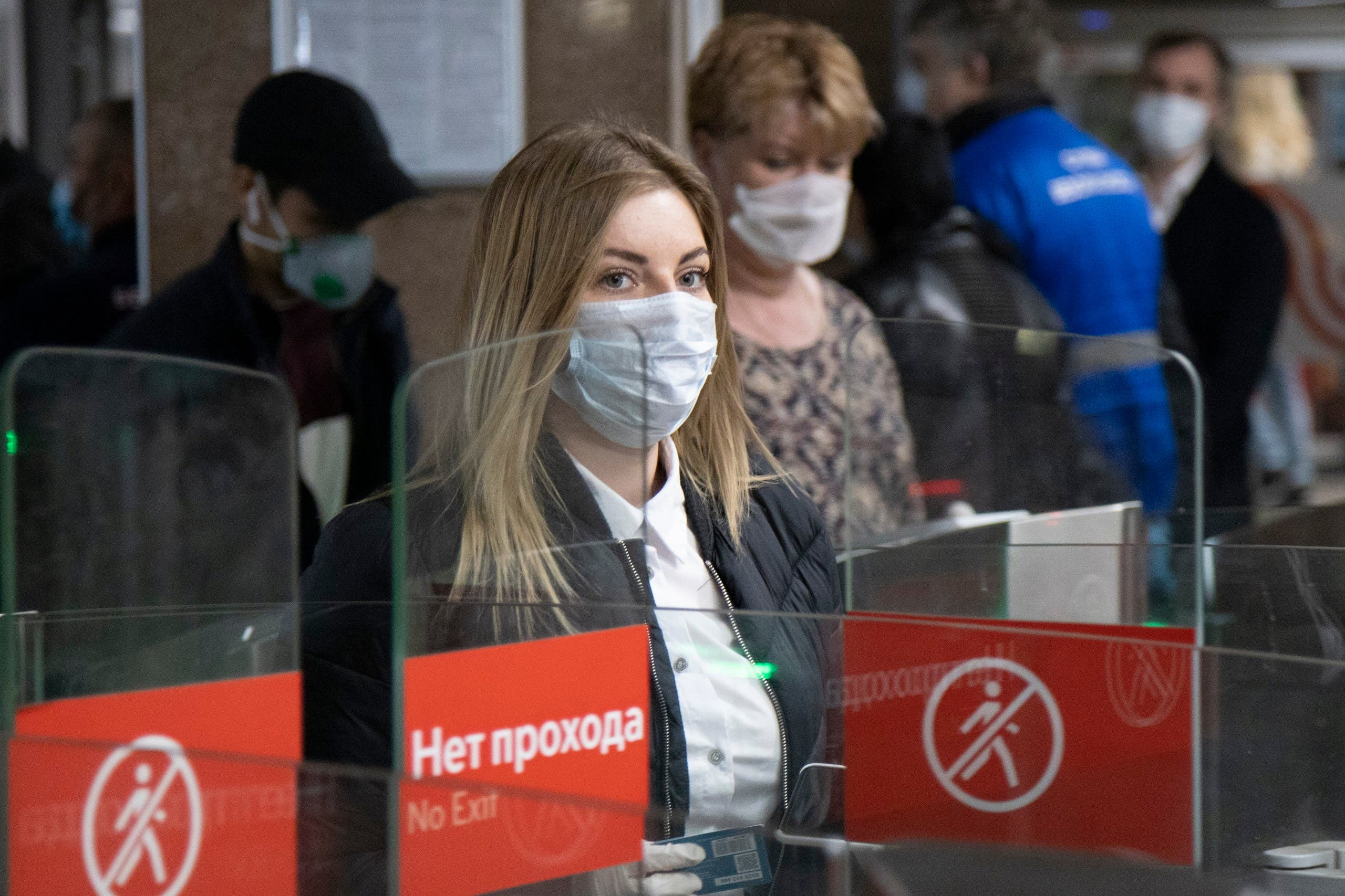 People wearing face masks and gloves to protect against coronavirus, observe social distancing guidelines as they pass through the turnstiles of the subway in Moscow, Russia on May 12, 2020. (AP)