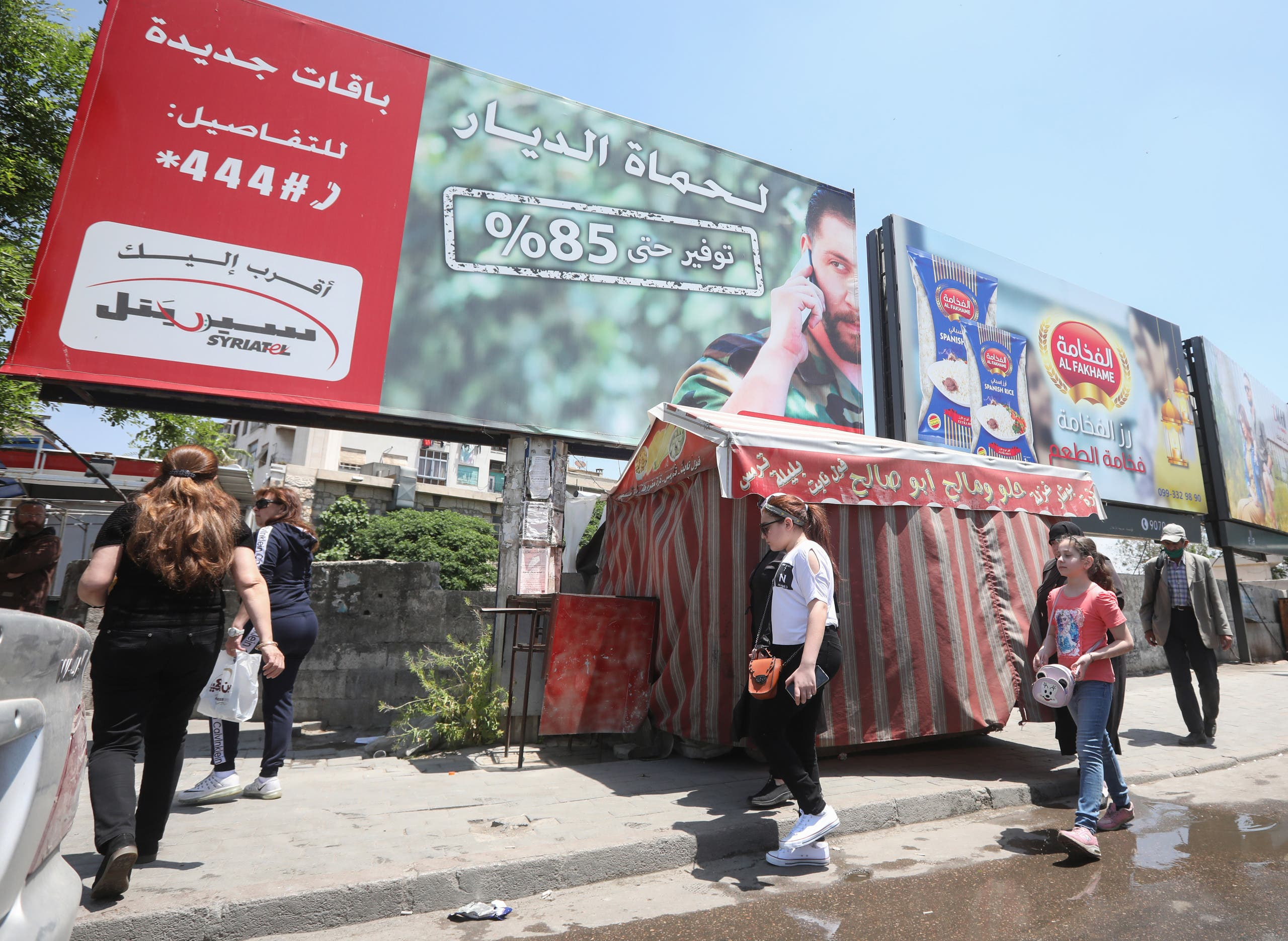 People walk underneath an advertising billboard of Syria's largest mobile operator Syriatel, owned by businessman Rami Makhlouf, in the Syrian capital Damascus on May 11, 2020. (Reuters)