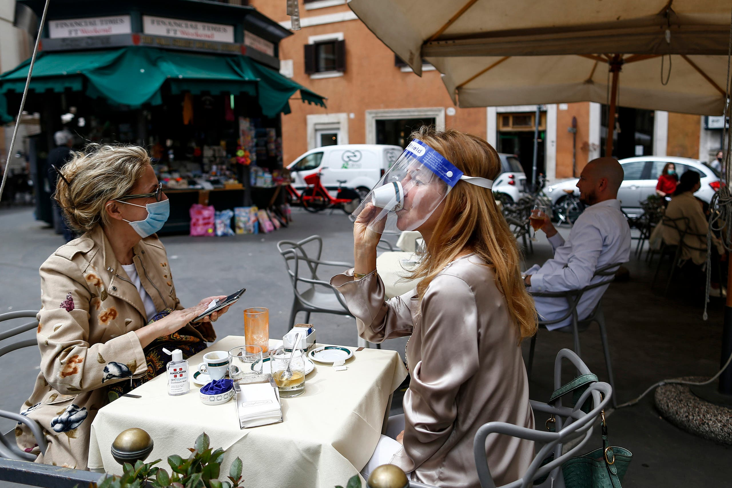A woman sips her coffee from under her facial protection at a cafe with outdoor tables in Rome on May 18, 2020. (AP)