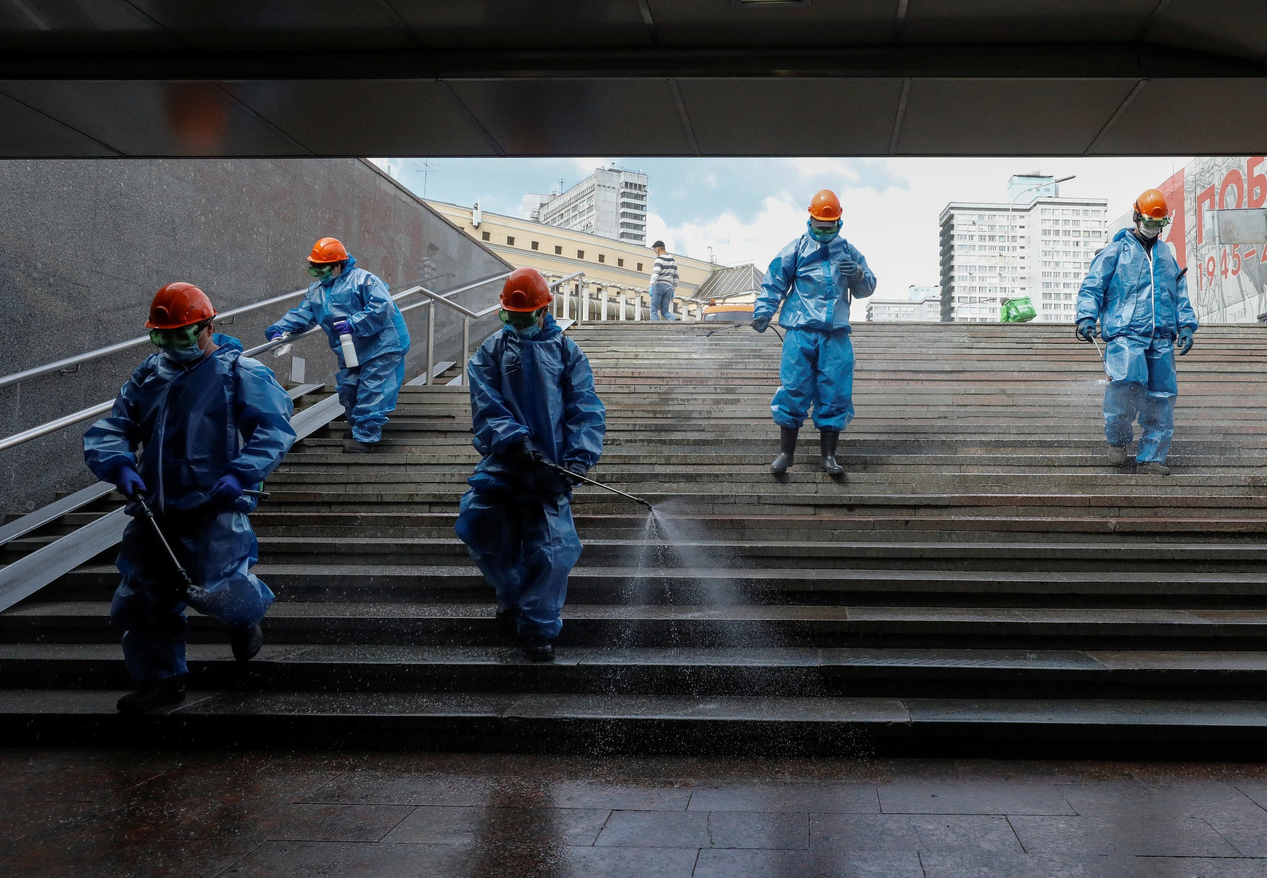 Specialists wearing protective gear spray disinfectant while sanitizing an underground passage amid the outbreak of the coronavirus disease (COVID-19) in Moscow, Russia May 16, 2020. (Reuters)