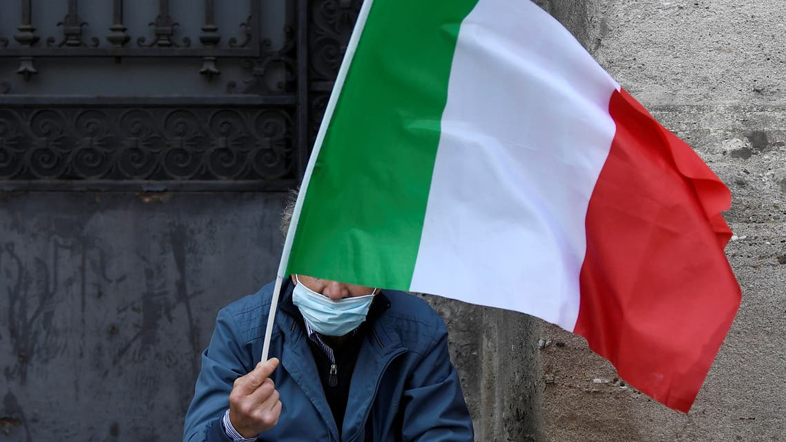 A man holds a flag as he takes part in a protest in front of the Alla Scala theatre, as Italy eases some of the lockdown measures put in place during the coronavirus disease (COVID-19) outbreak, in Milan, Italy May 18, 2020. REUTERS/Flavio Lo Scalzo