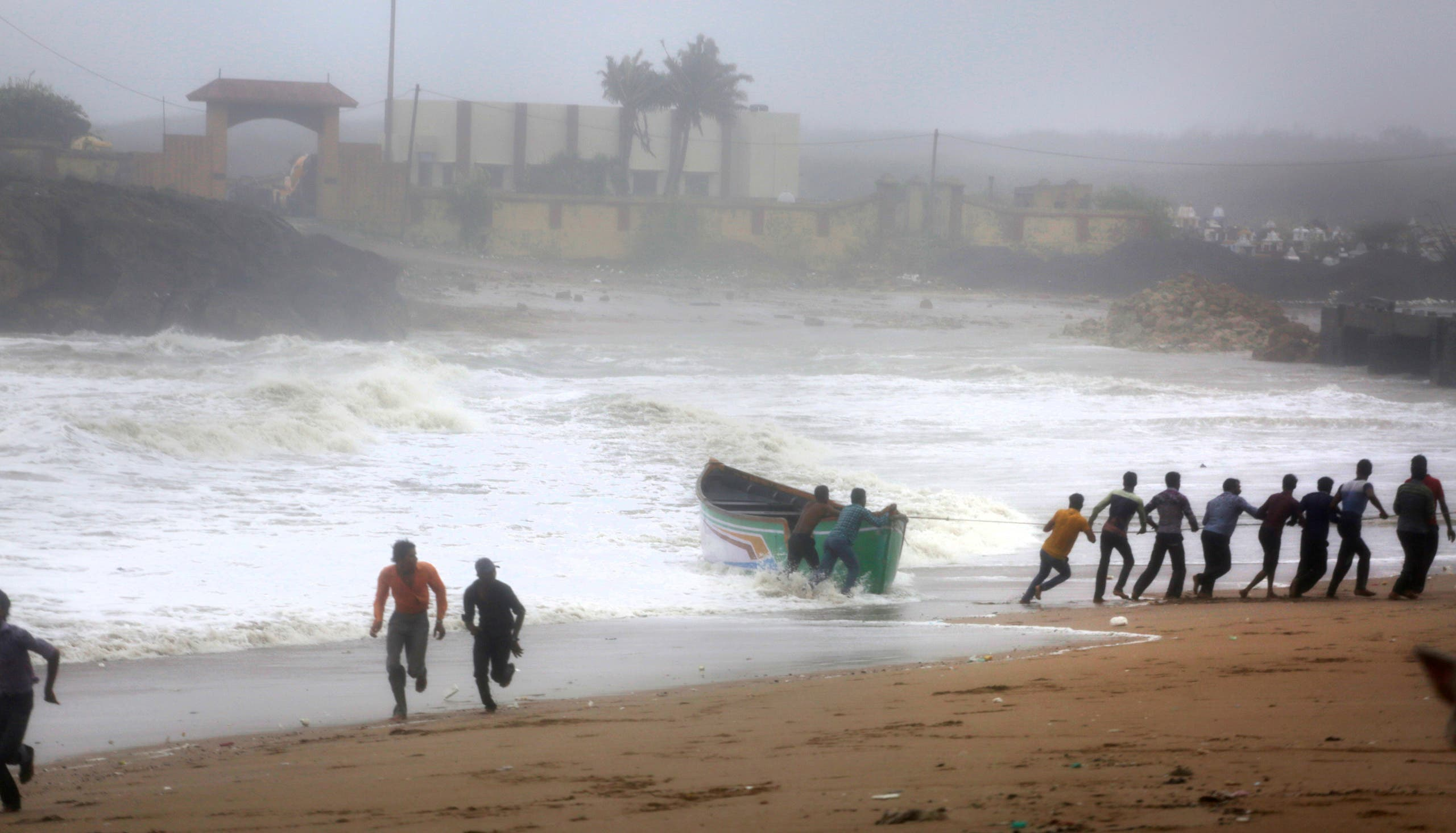 People try to pull back a fishing boat that was carried away by waves on the Arabian Sea coast as others run to take shelter in Veraval, Gujarat, India, on June 13, 2019. (AP)