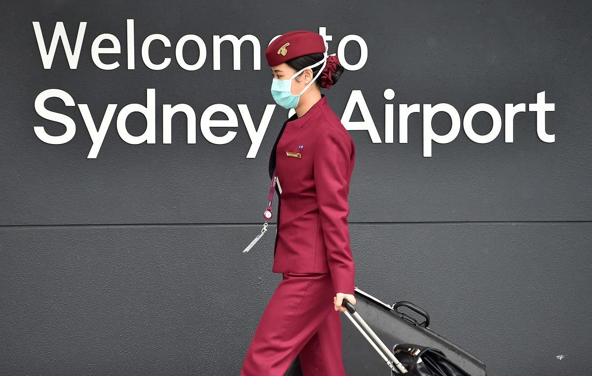 A Qatar Airways crew member enters Sydney international airport to fly on a repatriation flight back to France on April 2, amid the coronavirus pandemic. (AFP)