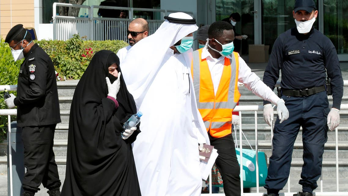 Qatari police stand outside a hotel in Doha as a medical worker walks alongside people wearing protective masks over fears of coronavirus, on March 12, 2020. (AFP)