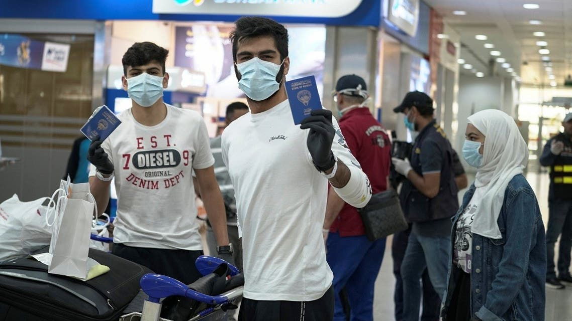 Kuwaiti boys wearing protective face masks and quarantine tracking bracelets, following the outbreak of the coronavirus disease (COVID-19), pose for the camera as they hold up their passports upon arrival from Amman, to Kuwait Airport in Kuwait. (Reuters)