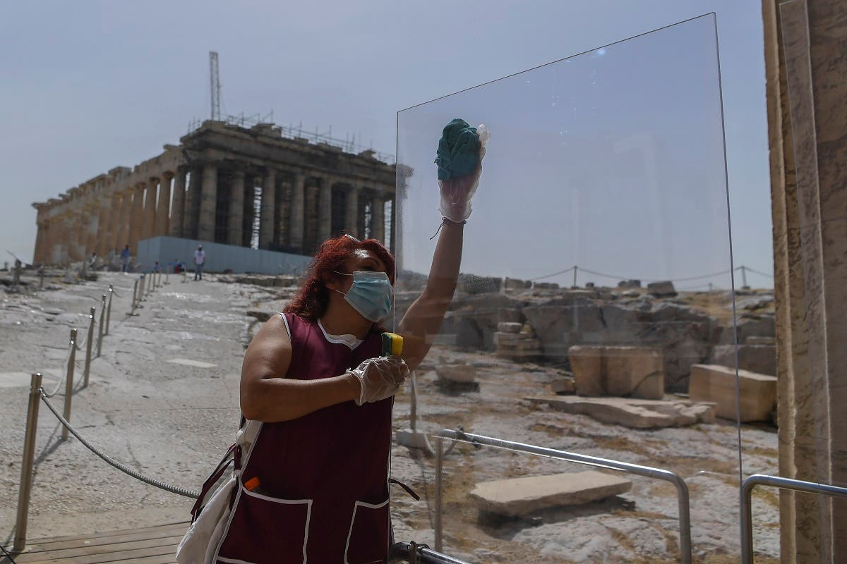 A worker wearing a protective mask cleans a divider made of plexiglass at the entrance of the Acropolis in Athens on May 18, 2020. (AFP)