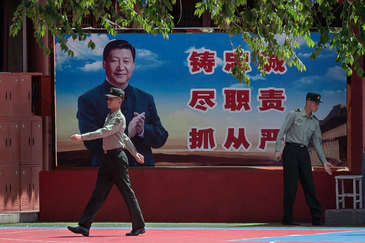 People's Liberation Army soldiers are seen next to a poster with a picture of Chinese President Xi Jinping next to the entrance to the Forbidden City in Beijing on May 18, 2020. (AFP)