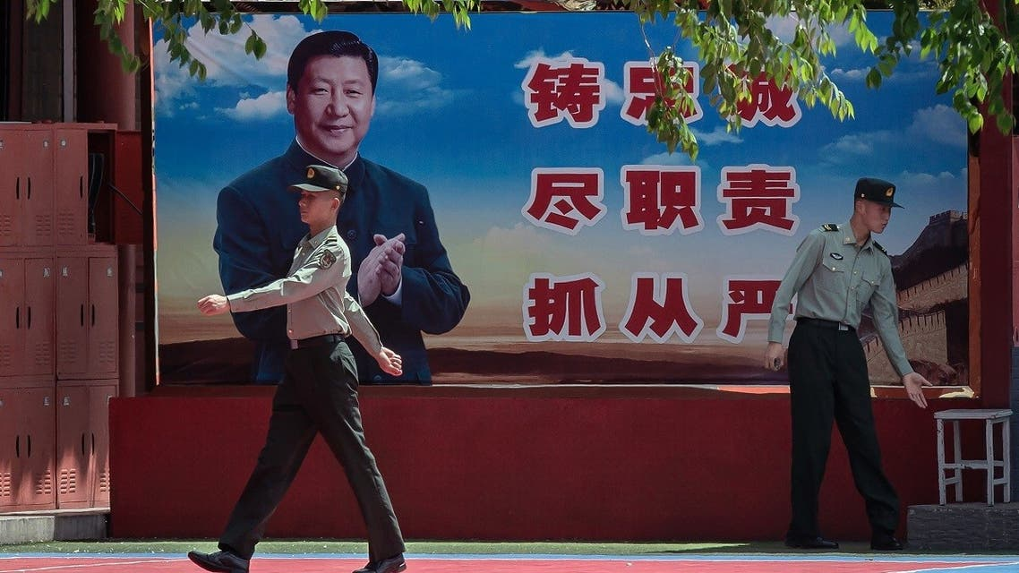 People's Liberation Army (PLA) soldiers are seen next to a poster with a picture of Chinese President Xi Jinping next to the entrance to the Forbidden City in Beijing on May 18, 2020. (AFP)