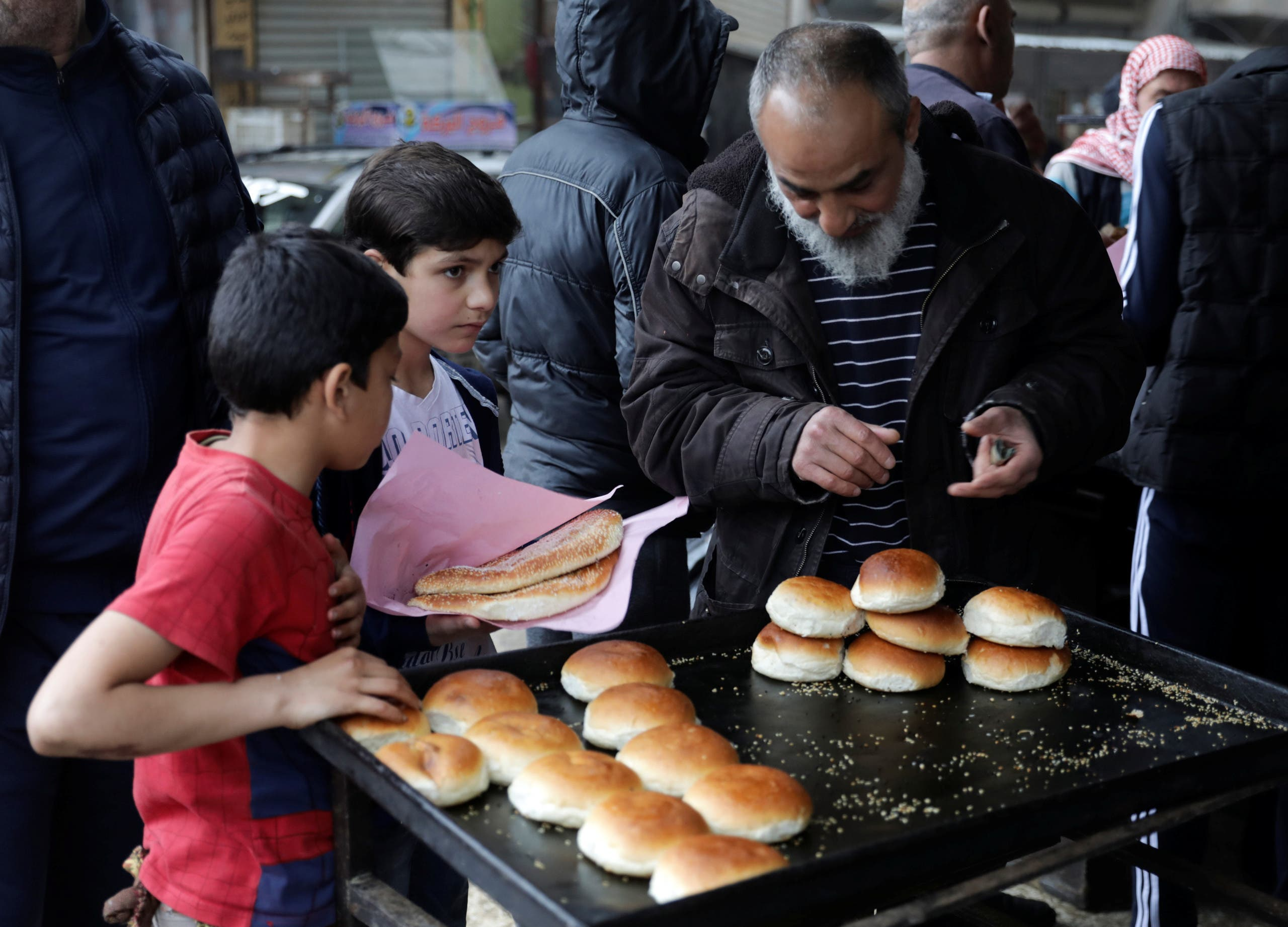 People buy traditional bread at a bakery before the time for iftar, or breaking fast, on the first day of the holy month of Ramadan, as the spread of the coronavirus disease (COVID-19) continues, in the rebel-held Idlib city, Syria April 24, 2020. (Reuters)