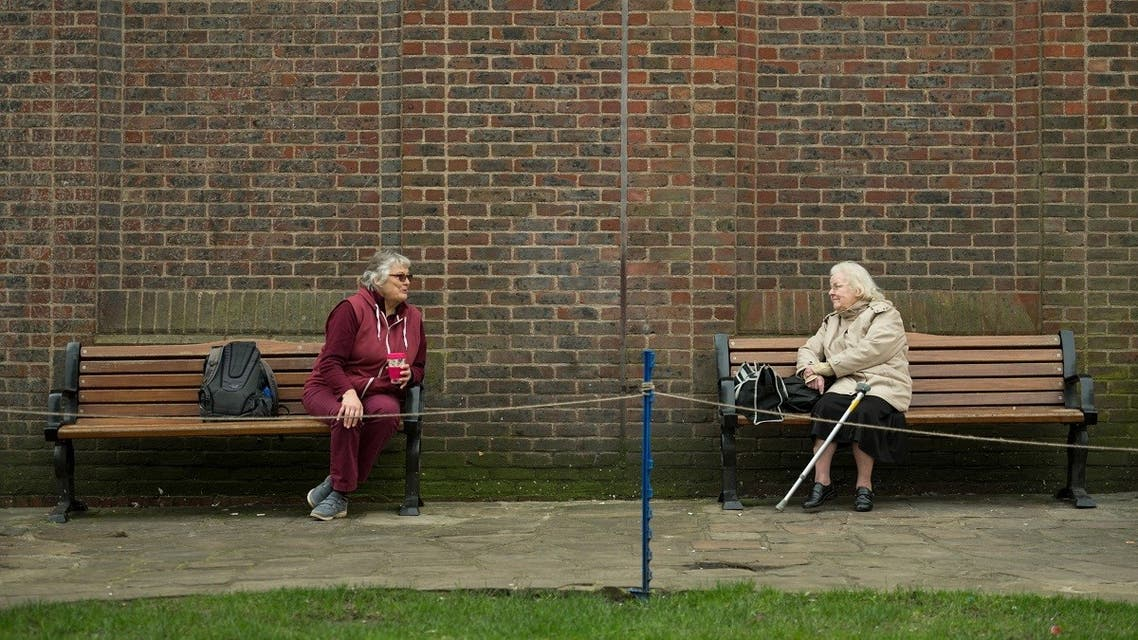 Two women observe social distancing measures as they speak to each other from adjacent park benches in the center of York, northern England on March 19, 2020. (AFP)