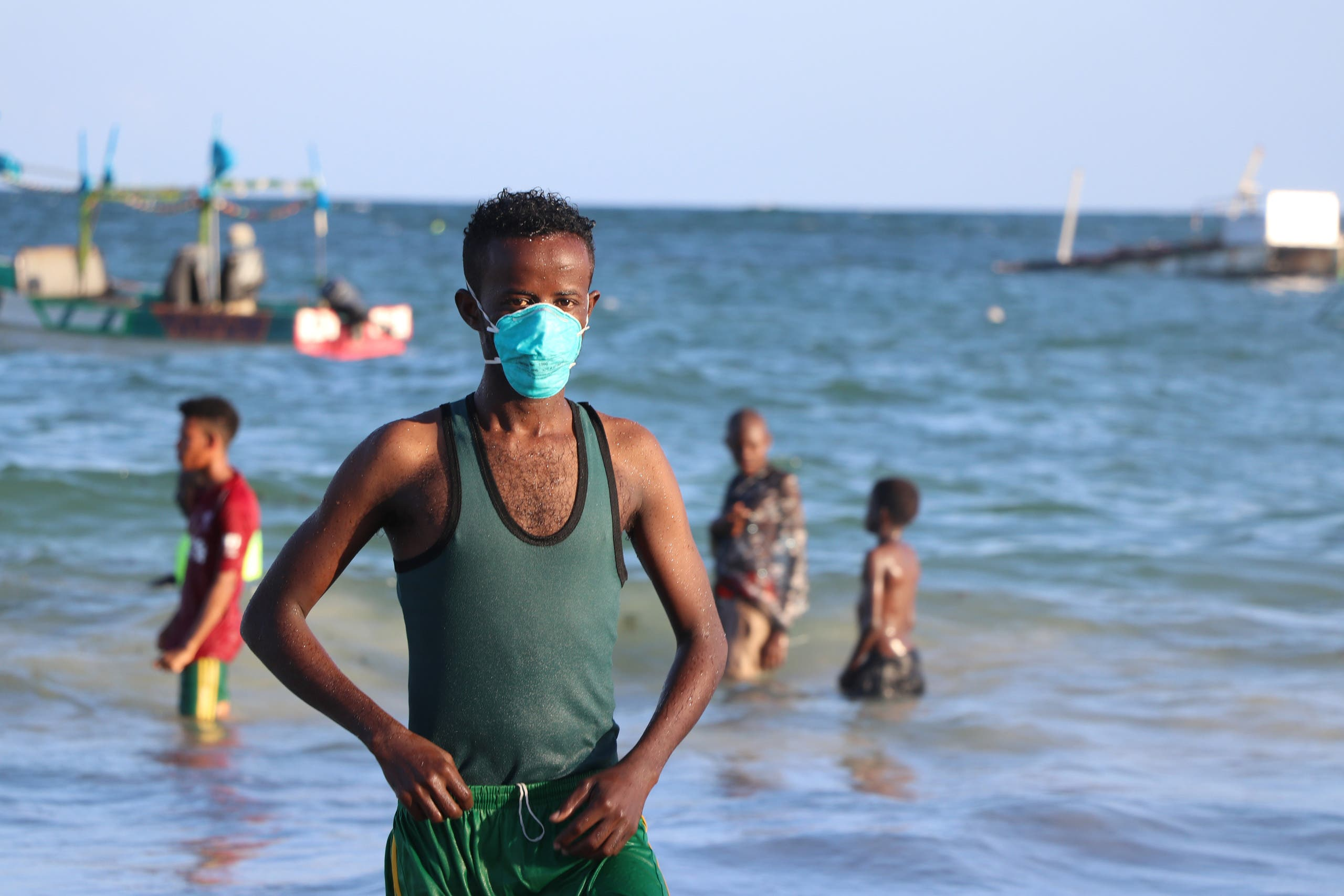A man wears a mask as a protective measure to curb the coronavirus while bathing at Lido beach in Mogadishu, Somalia, on April 4, 2020. (AFP)