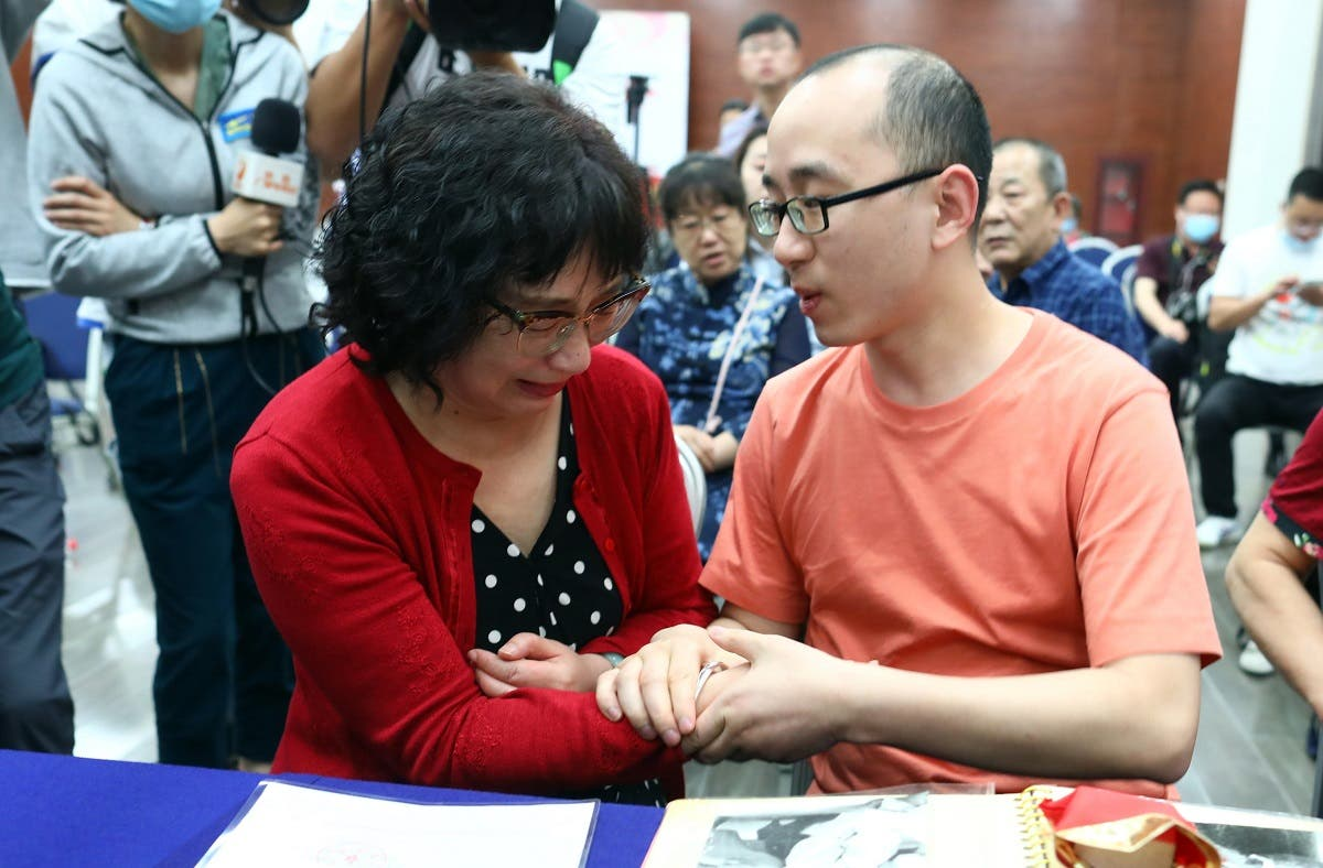 Mao Yin (R) with his mother Li Jingzhi after they were reunited in Xian, in China's northern Shaanxi province. (AFP)