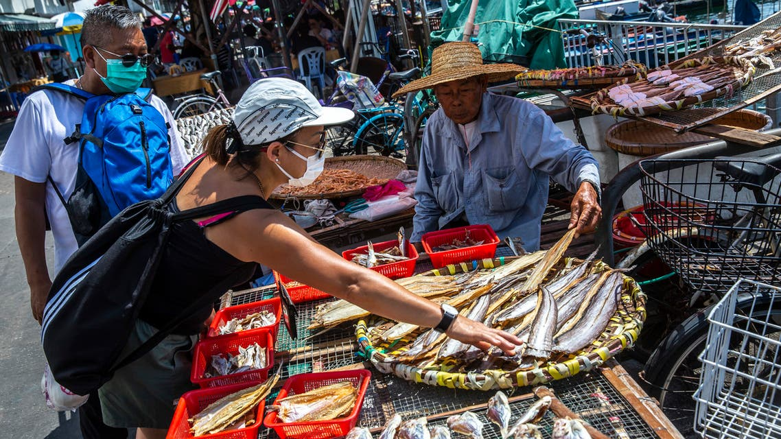 A man (R) sells dried seafood on Cheung Chau Island in Hong Kong on May 3, 2020. (AFP)