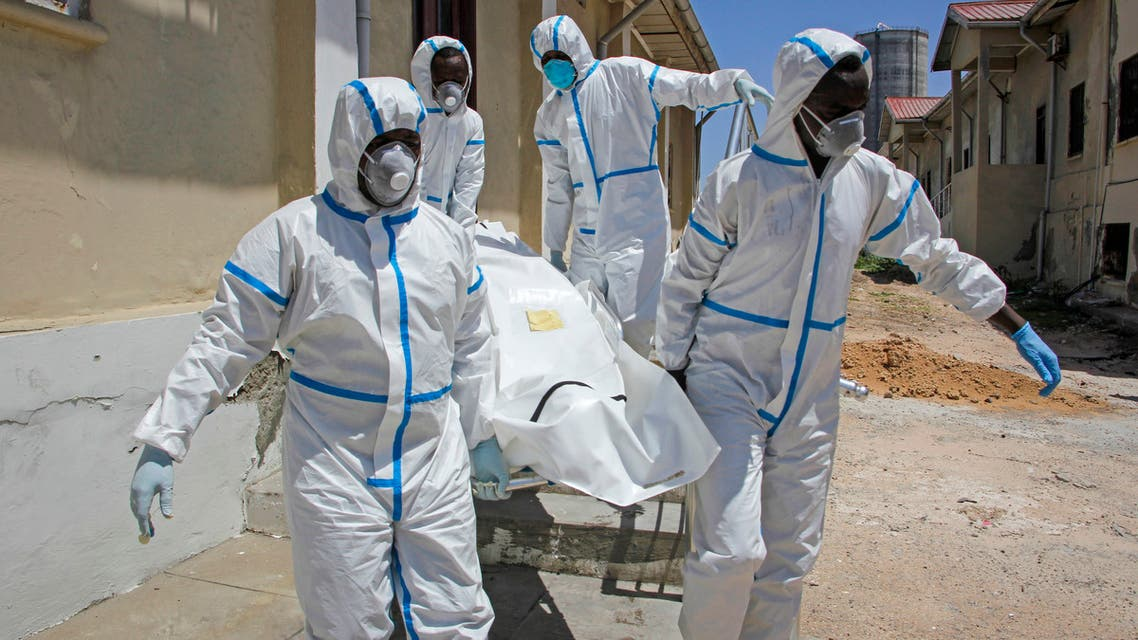 Medical workers in protective suits carry the body of a man who died of COVID-19, before he is buried in Mogadishu, Somalia on May, 13, 2020. (AP)