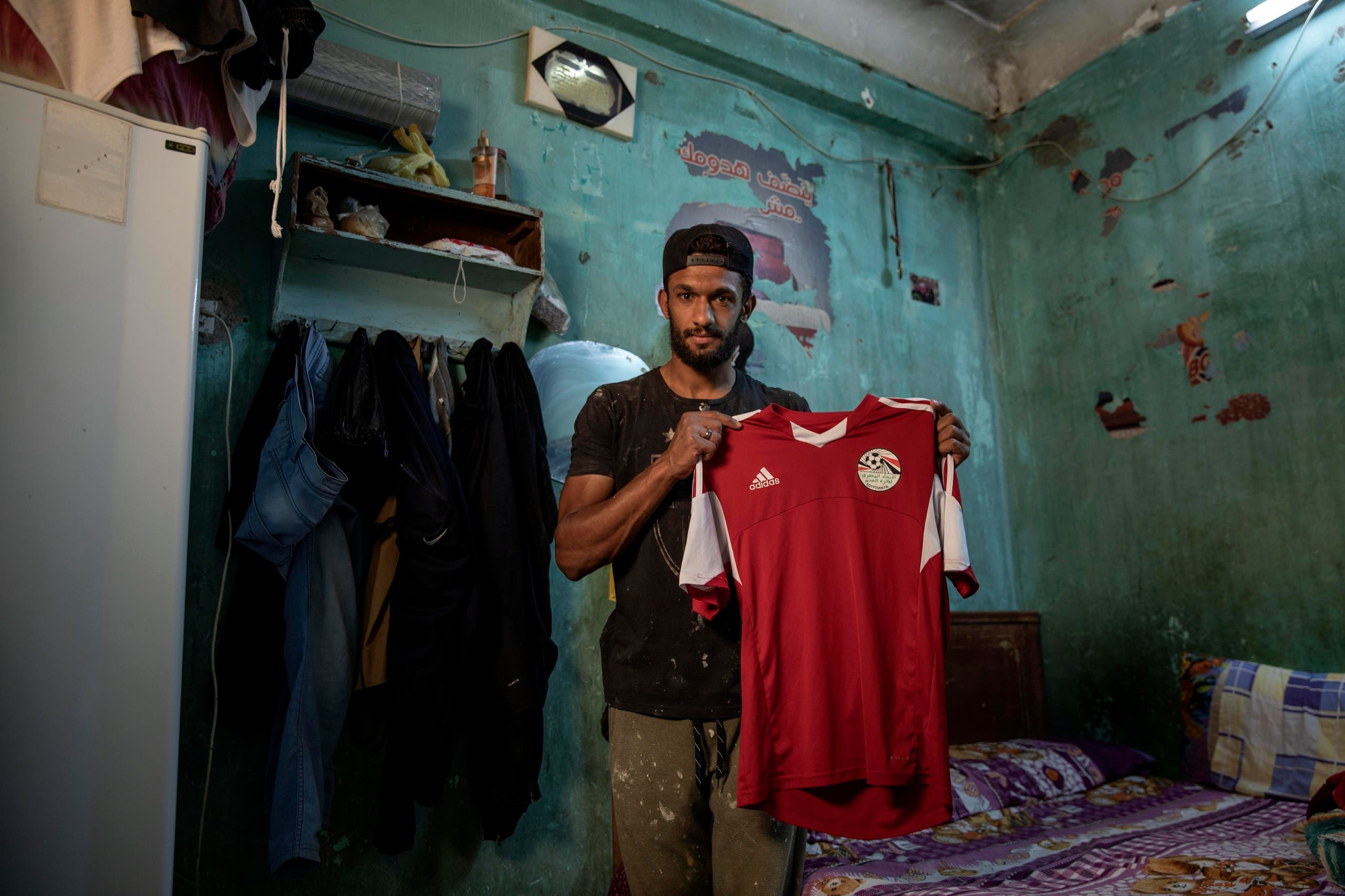 28-year-old defender Mahrous Mahmoud holds up his Egyptian national football team jersey he trains with, inside his home, in Manfalut, Egypt. (AP)