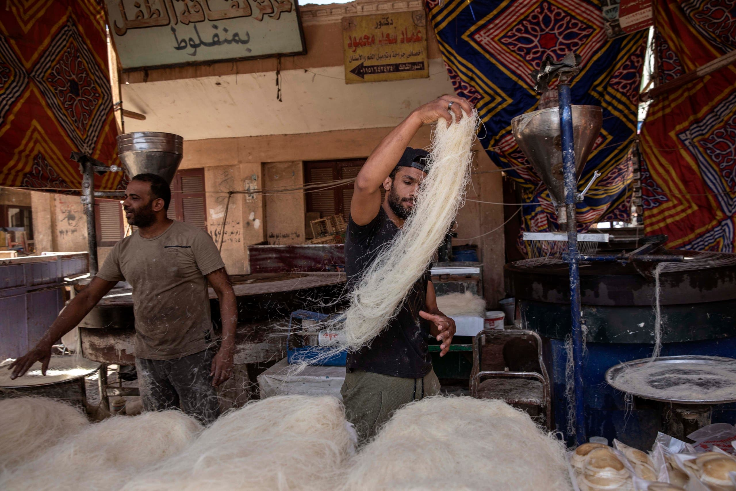 28-year-old football defender Mahrous Mahmoud, right, makes Ramadan sweets at a souq, in Manfalut, Egypt. (AP)