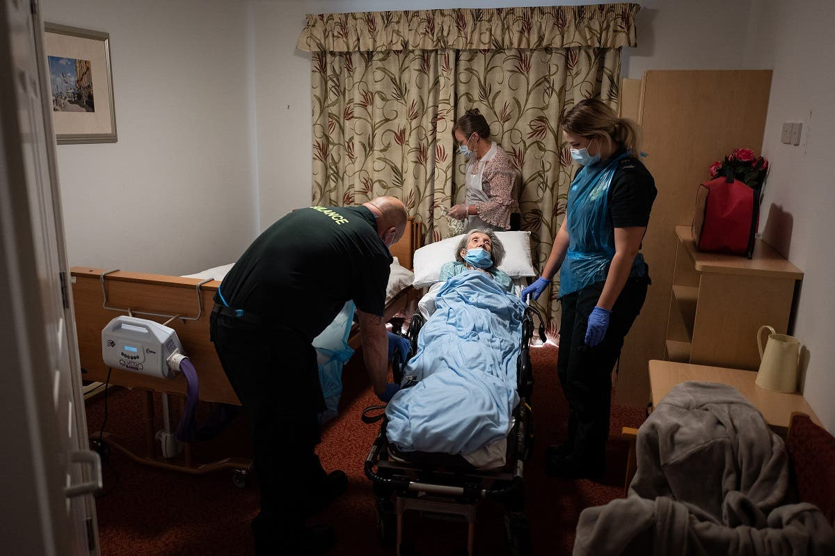 Medics help to settle an elderly non-COVID-19 patient into a care home after moving her from hospital near Portsmouth, south England on May 5, 2020. (AFP)