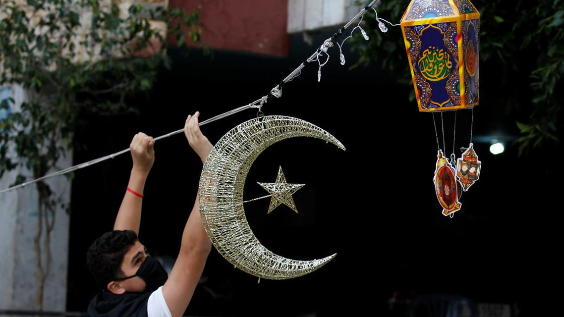 A man puts Ramadan decorations on a street ahead of the Muslim holy month of Ramadan, during a countrywide lockdown over the coronavirus disease (COVID-19) in Beirut. (Reuters)