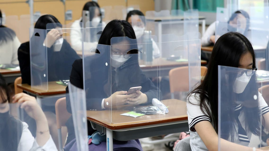 High school students wearing face masks prepare for classes, with plastic covers placed on desks to prevent infection, as schools reopen following the global outbreak of the coronavirus disease (COVID-19), in Daejeon, South Korea. (Reuters)