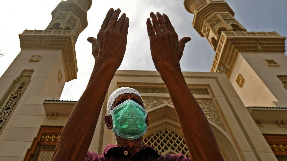 An elderly man wearing a protective mask prays outside a mosque which has been closed to worshipers amid the coronavirus pandemic, in Sharjah, UAE, March 30, 2020. (AFP)