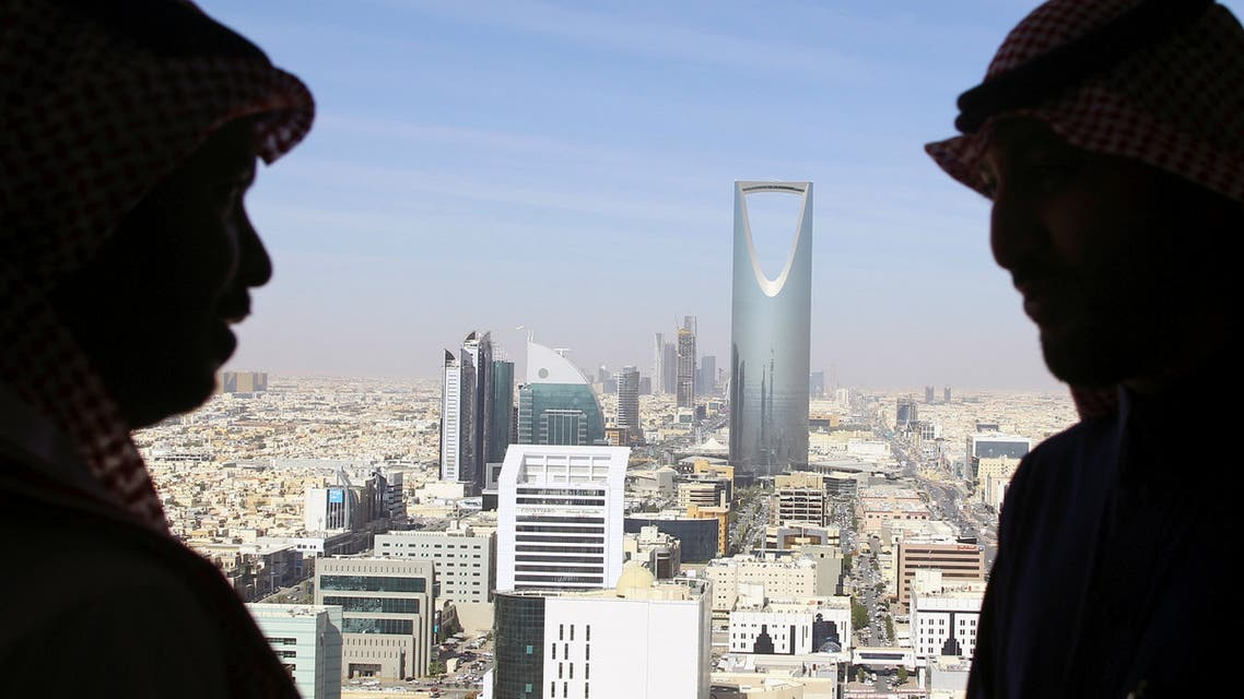 Men look out of a building as the Kingdom Centre Tower is seen in Riyadh, Saudi Arabia, January 1, 2017. (Reuters)