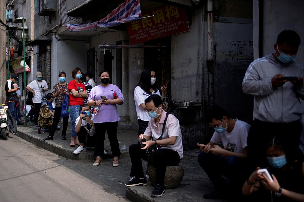 Residents wearing face masks line up for nucleic acid testings at a residential compound in Wuhan, the Chinese city hit hardest by the coronavirus disease (COVID-19) outbreak, Hubei province, China May 17, 2020. (Reuters)