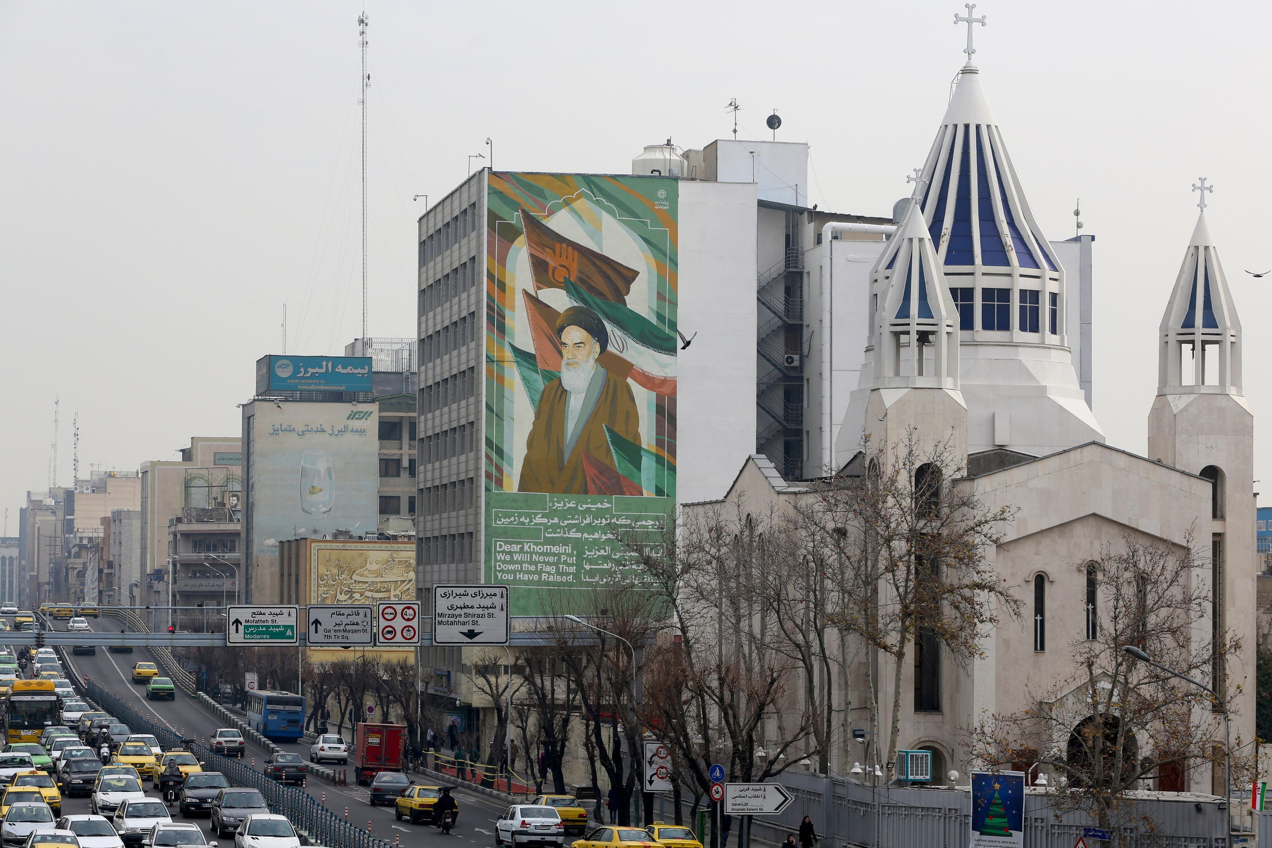 The Saint Sarkis Armenian Cathedral, next to a building bearing a drawing of the late founder of the Islamic Republic Ruhollah Khomeini, in Tehran on January 1, 2020. (AFP)