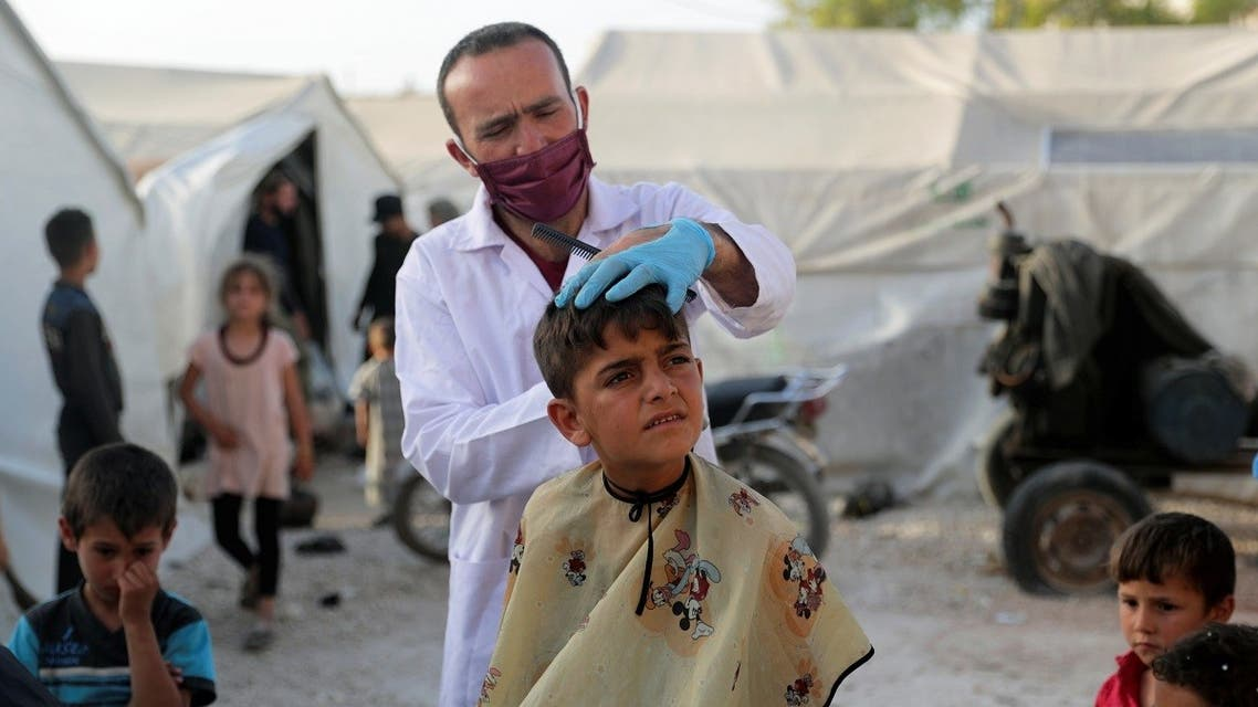 A volunteer hairdresser from ONSUR wearing a face mask and gloves cuts the hair of an internally displaced boy, ahead of the Eid al-Fitr at an IDP camp in Idlib, Syria May 19, 2020. (Reuters)