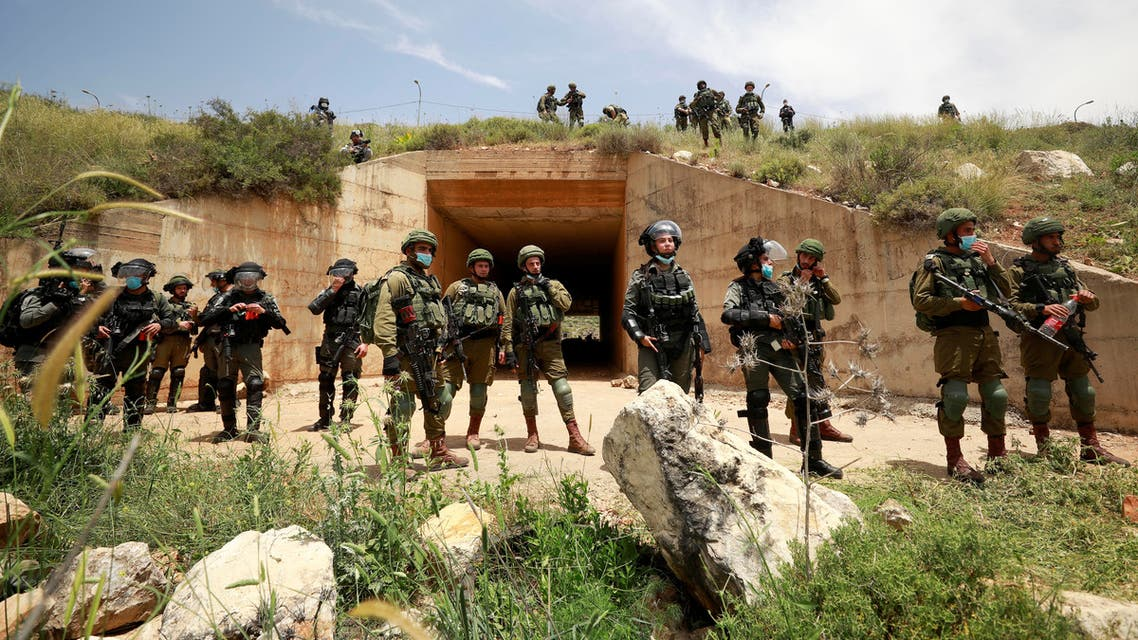 Israeli troops stand guard as Palestinians marking the 72nd anniversary of Nakba and protest against Israeli plan to annex parts of the occupied West Bank, in the village of Sawiya near Nablus May 15, 2020. (Reuters)