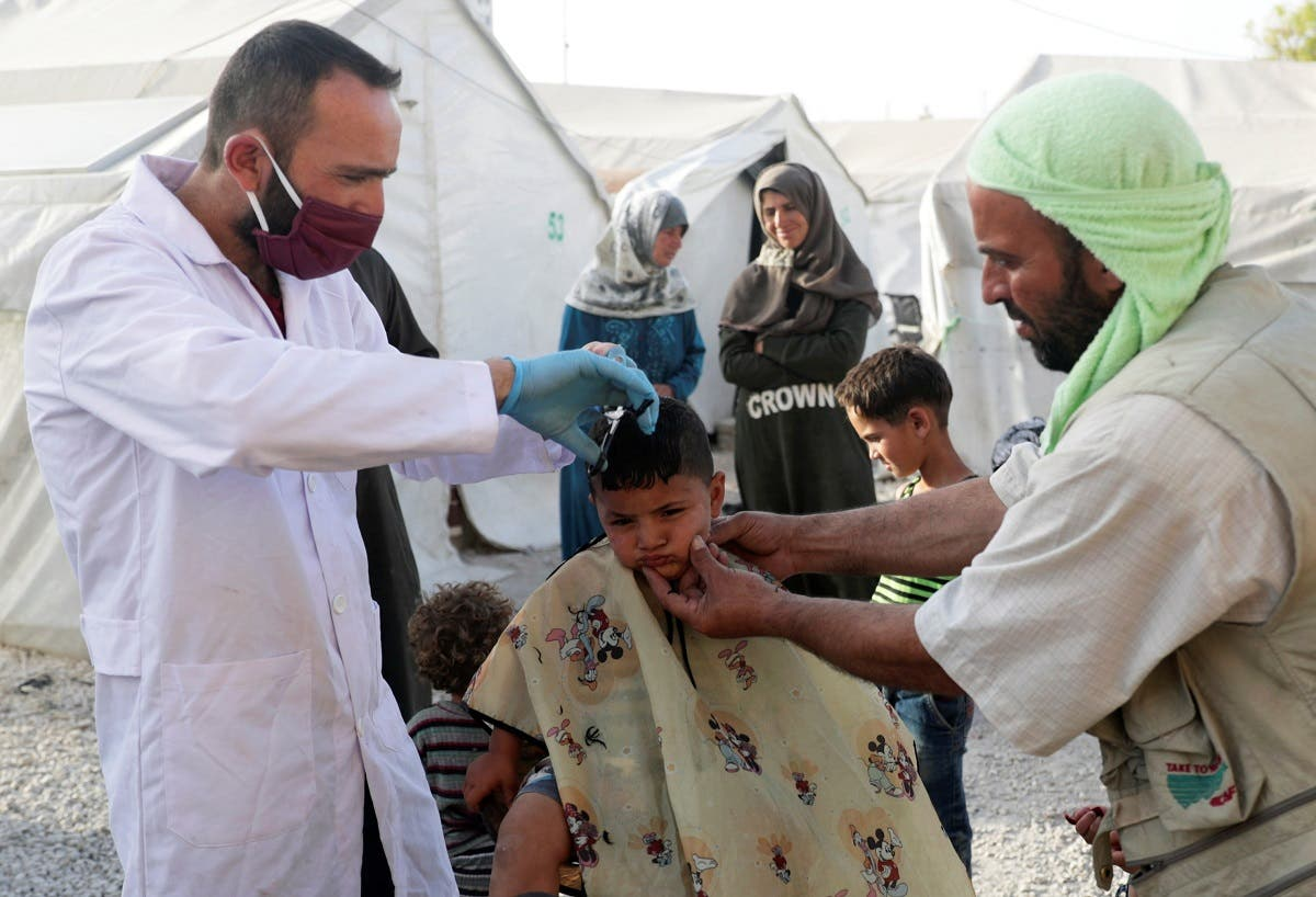 A volunteer hairdresser cuts the hair of an internally displaced boy at an IDP camp in Idlib, Syria May 19, 2020. (Reuters)