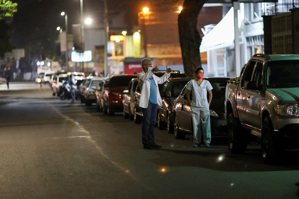 Doctors Carlos Martinez and Maria Martinez wait in line to get fuel at a gas station, during a nationwide quarantine due to the coronavirus, in Caracas, Venezuela April 7, 2020. (Reuters)