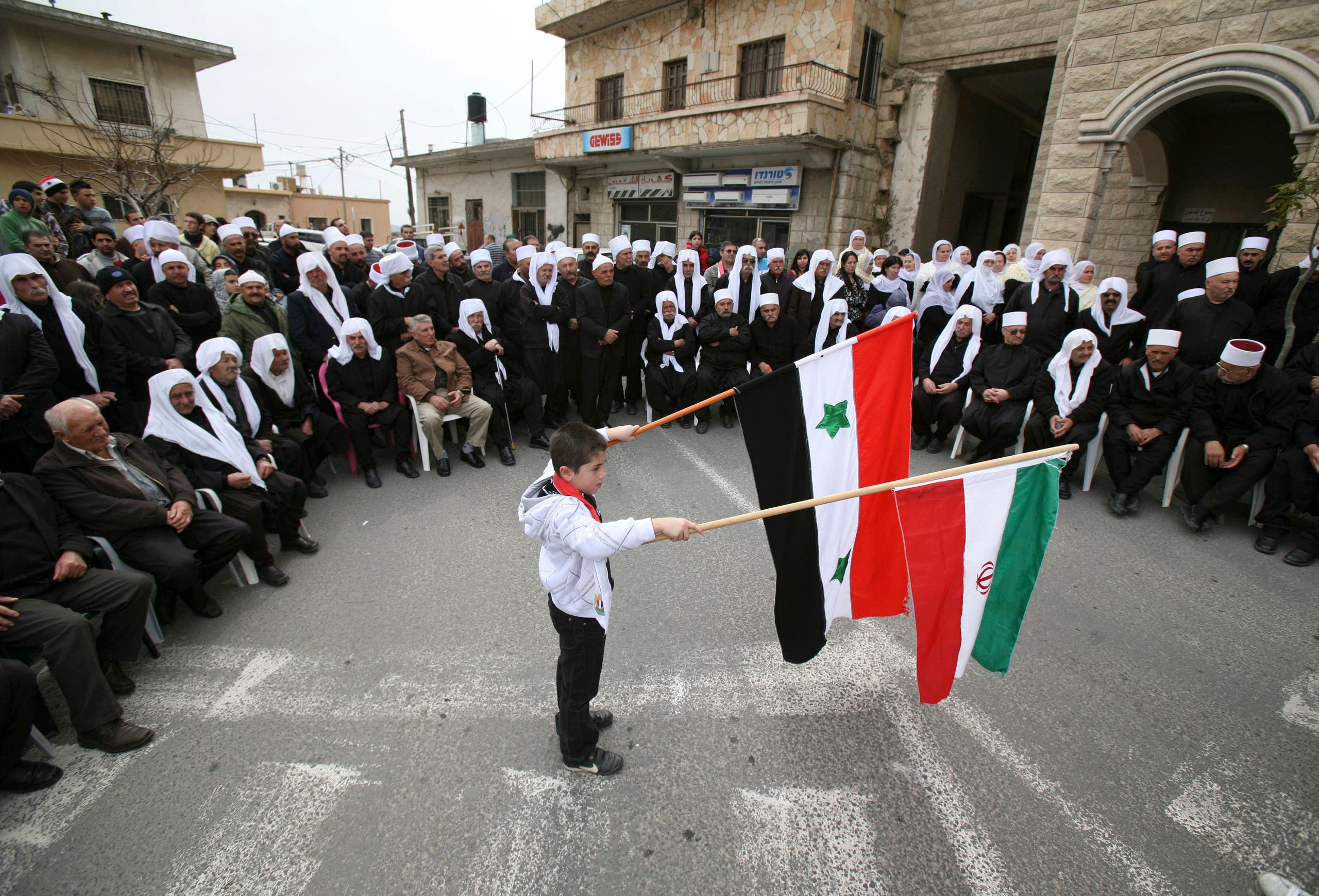 A boy holds flags of Iran and Syria during a rally in the Druze village of Majdal Shams on the Golan Heights, which stand at the heart of a long-standing conflict between Israel and Syria February 14, 2012. (File photo: Reuters)
