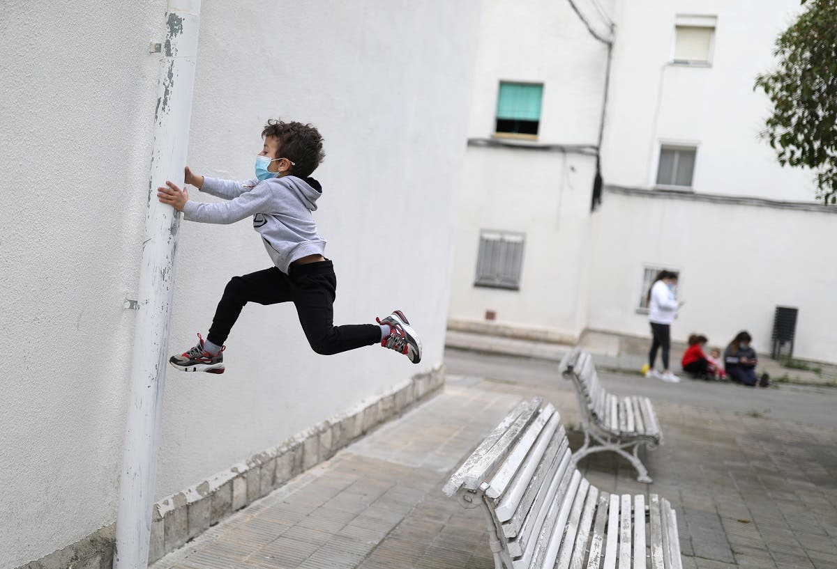 Kilian, 6, wears a protective face mask as he jumps from a bench, after restrictions were partially lifted for children, during the coronavirus disease (COVID-19) outbreak, in Igualada, Spain April 26, 2020. (Reuters)