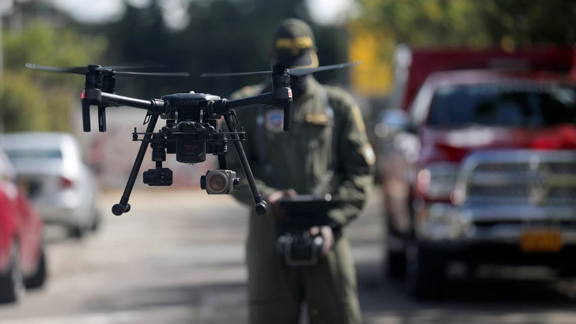 A Colombian police officer operates a drone that measures body temperature, in an area of ??high contagion amid the coronavirus disease (COVID-19) outbreak, in Bogota, Colombia May 20, 2020. REUTERS/Luisa Gonzalez
