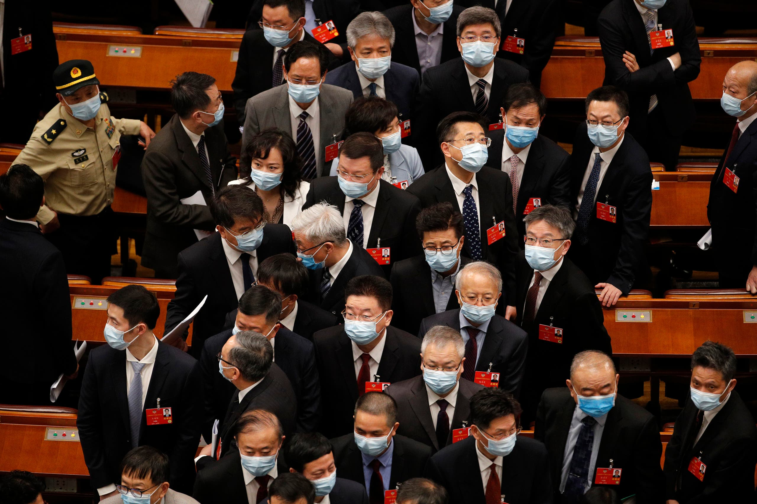 Delegates wearing face masks to protect against the spread of the new coronavirus leave after the opening session of the Chinese People's Political Consultative Conference (CPPCC) at the Great Hall of the People in Beijing on May 21, 2020. (AP)