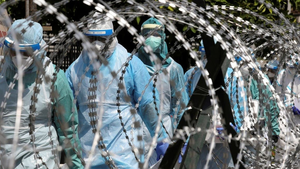 Medical workers wearing protective suits pass by barbed wire at the red zone under enhanced lockdown, amid the coronavirus outbreak in Petaling Jaya, Malaysia May 11, 2020. (Reuters)