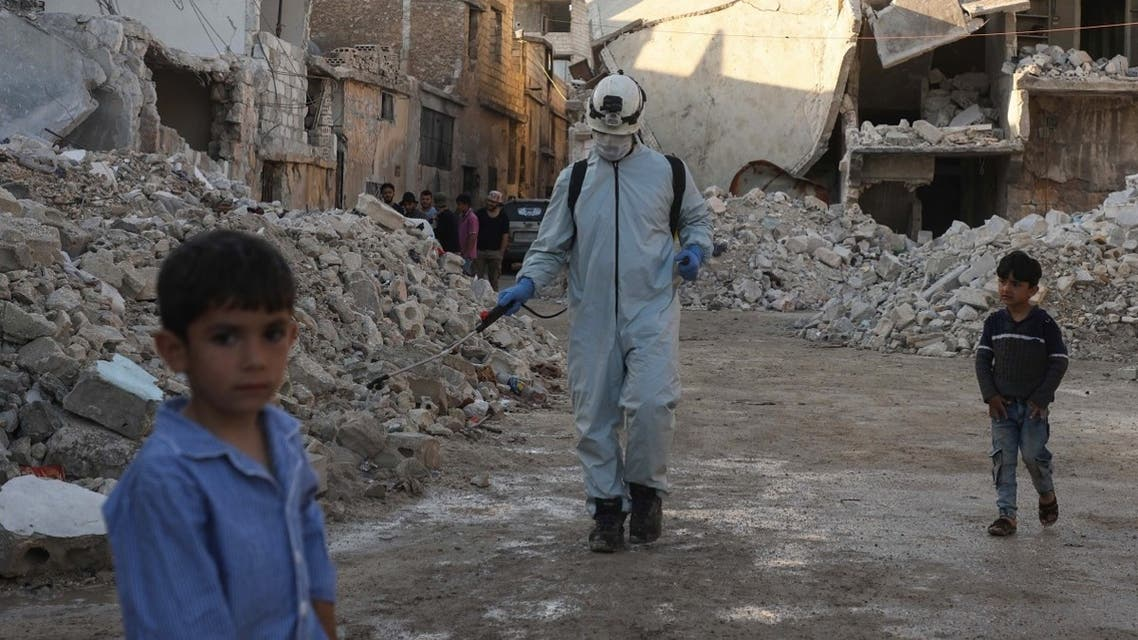 A member of the Syrian civil defense, also known as the White Helmets, disinfects a destroyed neighborhood in Atareb town of Syria's Aleppo province on May 7, 2020. (AFP)