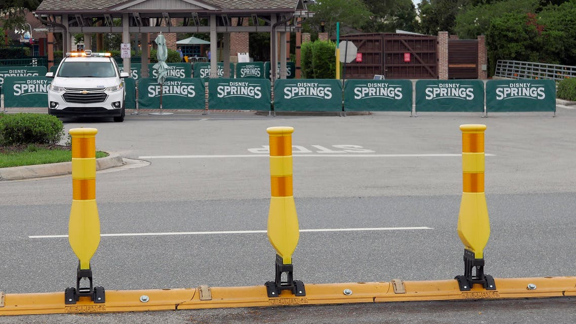 Barricades and a security vehicle block the entrance to a closed Disney Springs Monday, May 18, 2020, in Lake Buena Vista, Fla. As Walt Disney World shops and restaurants prepare to open at its entertainment complex later this week, it's posting a warning about the dangers of coronavirus advising guests that they voluntarily assume all risks related to exposure to COVID-19. (AP Photo/(John Raoux)