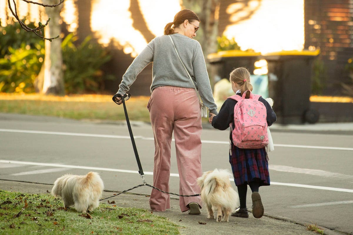 A school girl and her mum make their way to school after the government allowed schools to re-open under Level 2 guidelines in Wellington on May 18, 2020. (AFP)