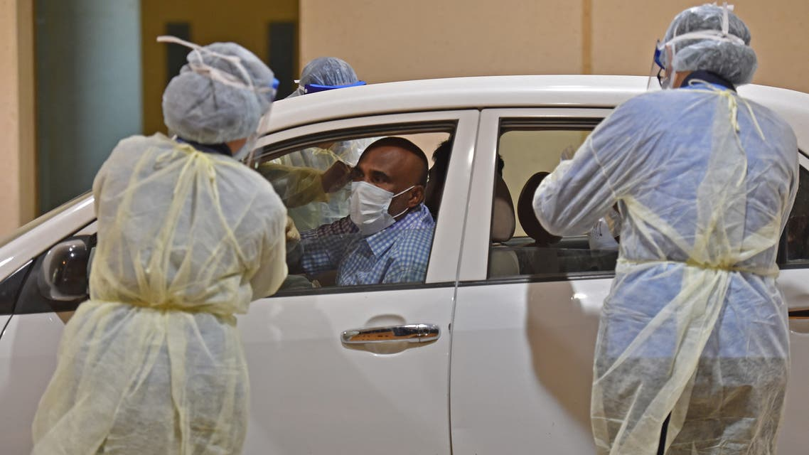 Health workers perform a nose swab test during a drive through coronavirus test campaign held in Diriyah hospital in the Saudi capital Riyadh on May 7, 2020 amid the COVID-19 pandemic.