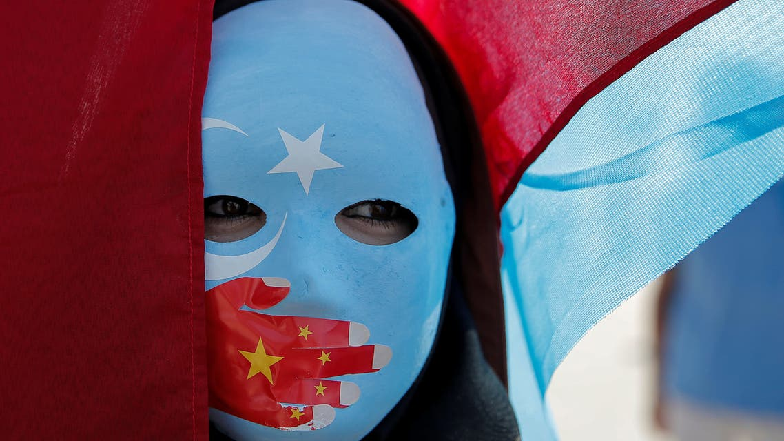An ethnic Uighur demonstrator wears a mask as she attends a protest against China in front of the Chinese Consulate in Istanbul. (Reuters)