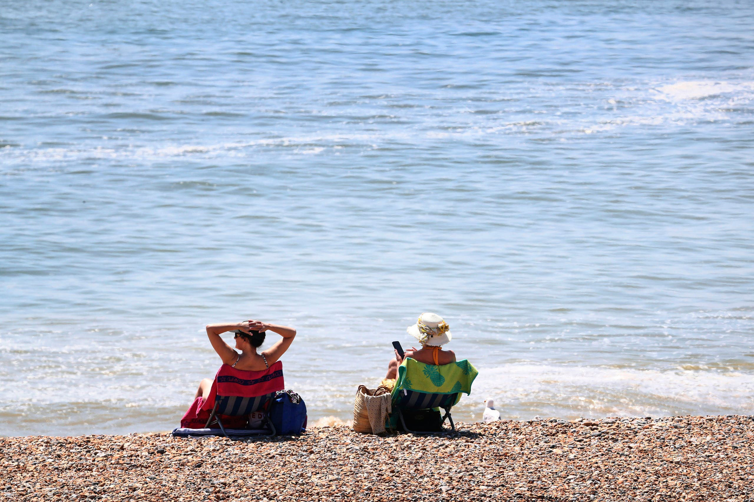 Women enjoy the good weather on the beach as lockdown measures due to the coronavirus outbreak were eased, in Brighton, England, on Thursday May 21, 2020. (AP)