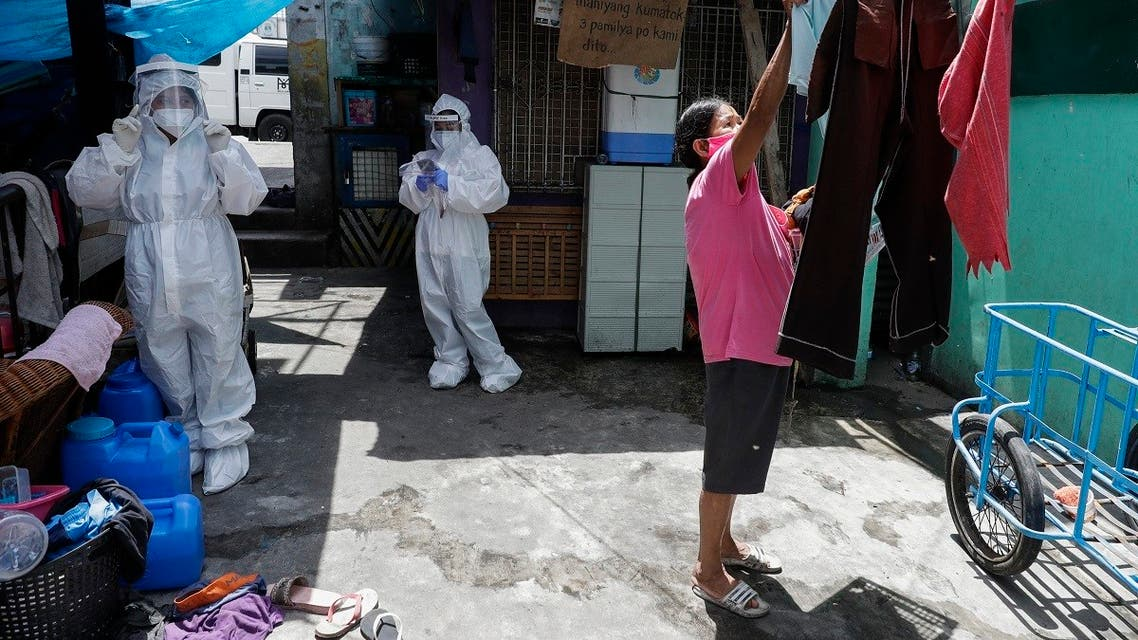 A woman arranges her laundry as health workers wearing protective suits visit a slum area to immunize small children against measles during a quarantine to prevent the spread of coronavirus in Manila, Philippines, May 5, 2020. (AP)