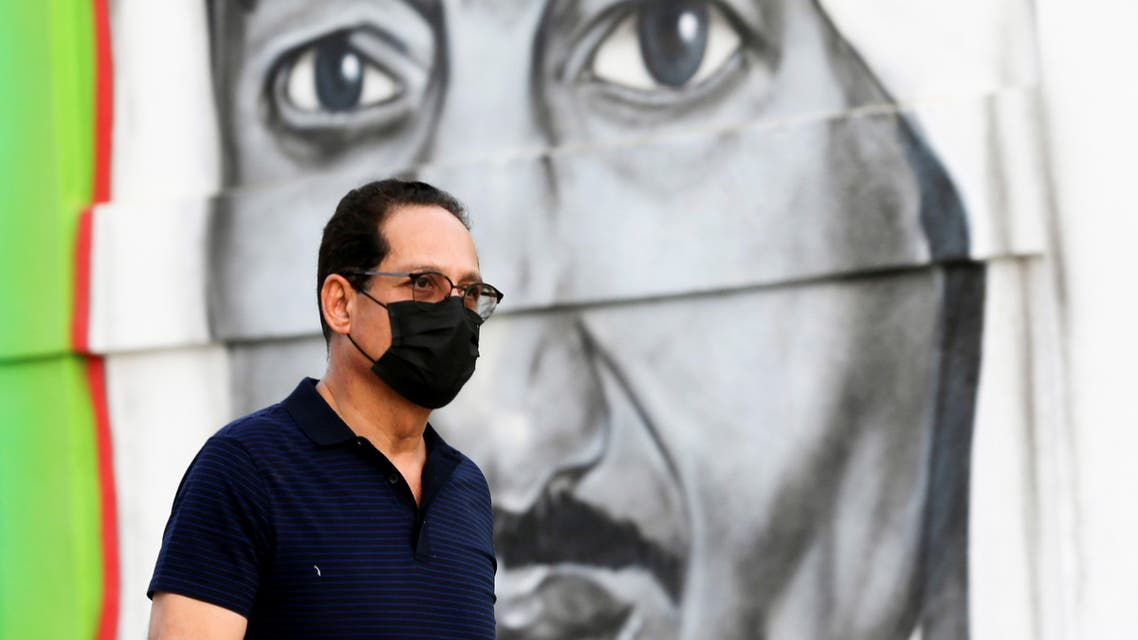 A Saudi man walks past a poster depicting Saudi King Salman bin Abdulaziz, after a curfew was imposed to prevent the spread of the coronavirus disease (COVID-19), in Riyadh. (Reuters)