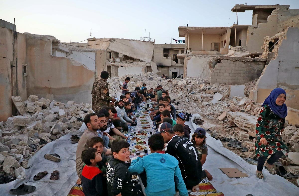 """This picture taken on May 12, 2020 in the village of Kafr Nuran in the western countryside of Syria's northern Aleppo province shows men and children seated together in the midst of ruins before starting the """"iftar"""" fast-breaking meal. (AFP)"""